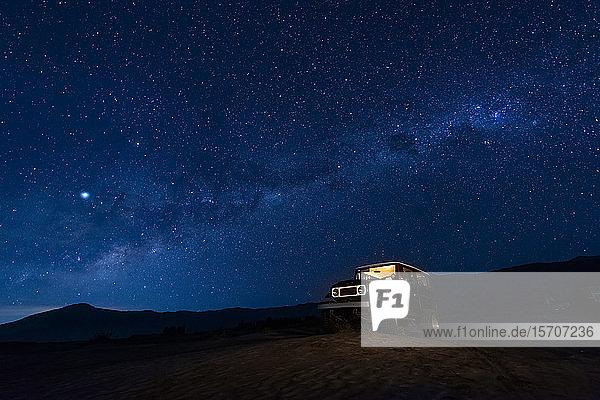 Indonesien  Ost-Java  Milchstrasse-Galaxie am blauen Sternenhimmel über dem im Bromo Tengger Semeru-Nationalpark geparkten Auto