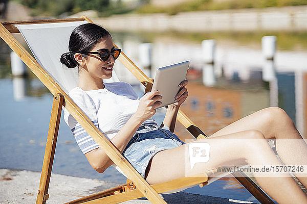 Lächelnde junge Frau sitzt in einem Liegestuhl und benutzt ein Tablett