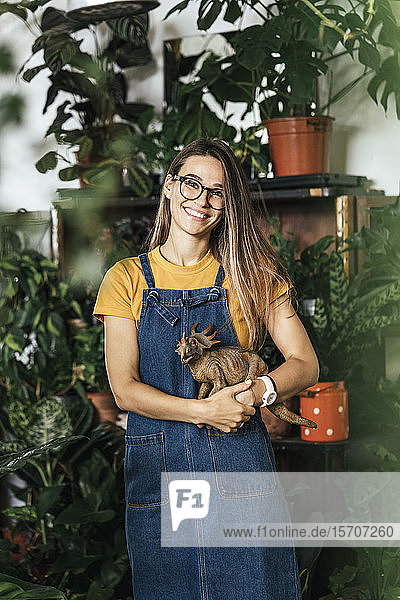 Portrait of a young woman holding dinosaur figurine in a small shop with plants