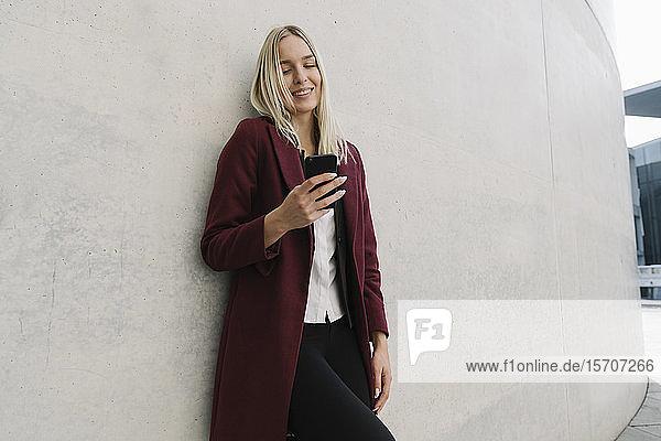 Blonde Geschäftsfrau  die ein Smartphone benutzt und sich an eine Wand lehnt