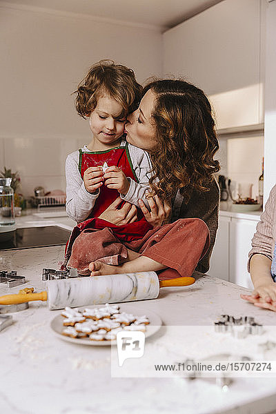 Mother kissing daughter in kitchen with Christmas cookies on counter