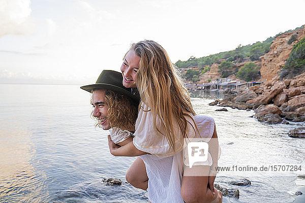 Junger Mann nimmt seine Freundin huckepack vor dem Meer mit  Ibiza  Balearen  Spanien