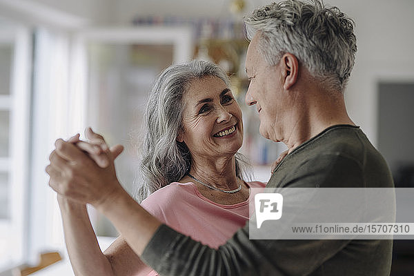 Happy senior couple dancing in living room at home