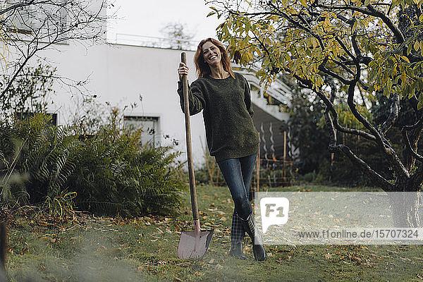 Frau  die in ihrem Garten arbeitet und eine Schaufel hält