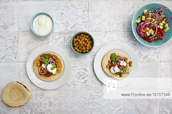 Israelischer Sabich mit Fladenbrot  Auberginen  Kichererbsen  Zwiebeln  Tomaten  Gurken  Joghurt und Zhug-Sauce
