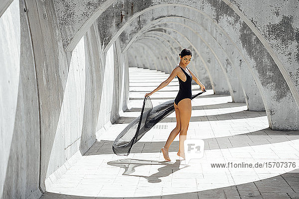 Junge Frau im schwarzen Badeanzug tanzt in einem Torbogen