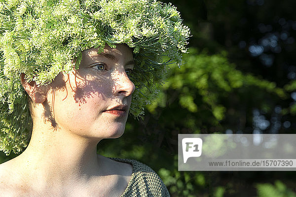 Portrait of young woman wearing headpiece of flowers