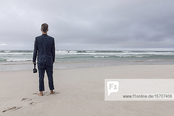 Back view of businessman standing on beach with VR glasses  Nordhoek  Western Cape  South Africa