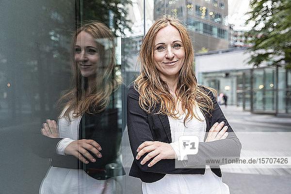 Porträt einer selbstbewussten Geschäftsfrau  die sich an ein Gebäude in der Stadt lehnt