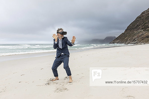 Businessman using VR glasses on the beach  Nordhoek  Western Cape  South Africa