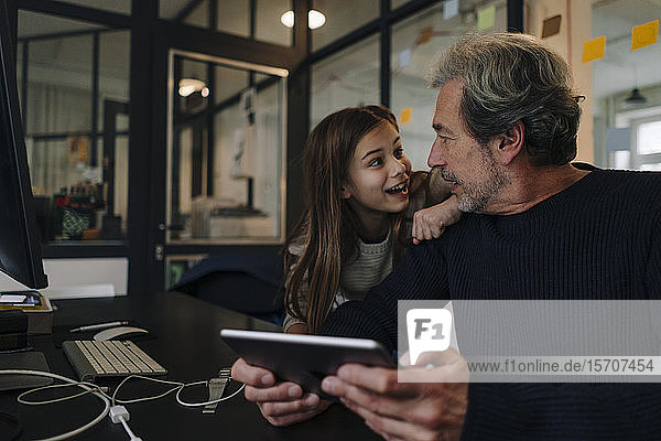 Casual senior buisinessman and girl with tablet in office