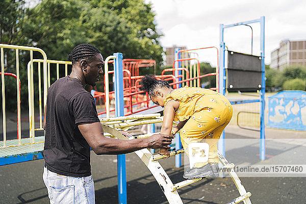Vater hilft Tochter beim Aufstieg auf eine Leiter auf einem Spielplatz