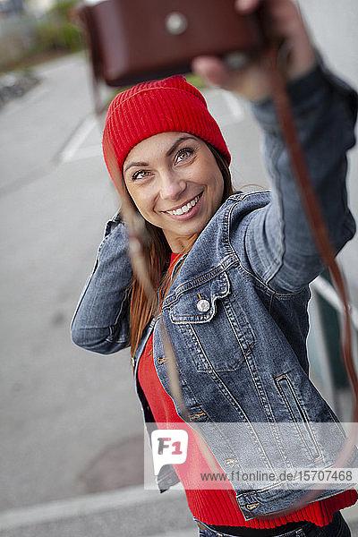 Frau mit rotem Pullover  Jeansjacke und Wollmütze  die einen Selfie trägt