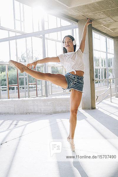 Ballerina mit Kopfhörer beim Tanzen in der Turnhalle