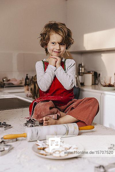 Porträt eines lächelnden Mädchens mit Weihnachtsplätzchen in der Küche