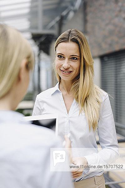 Porträt einer jungen Geschäftsfrau  die ihren Amtskollegen anlächelt