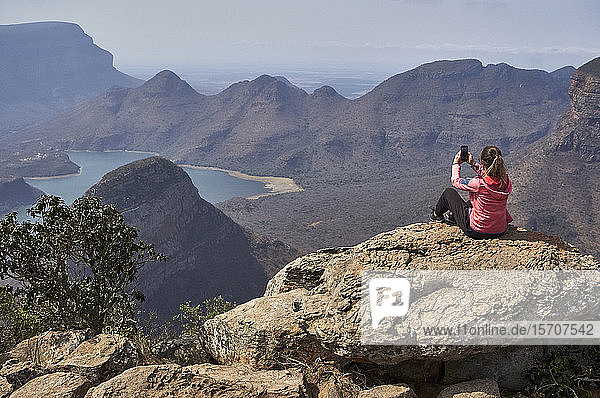 Woman taking a photo with her cell phone with a beautiful landscape background  Blyde River Canyon  South Africa