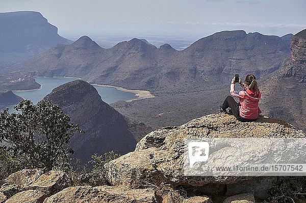 Frau fotografiert mit ihrem Mobiltelefon vor einem wunderschönen Landschaftshintergrund  Blyde River Canyon  Südafrika