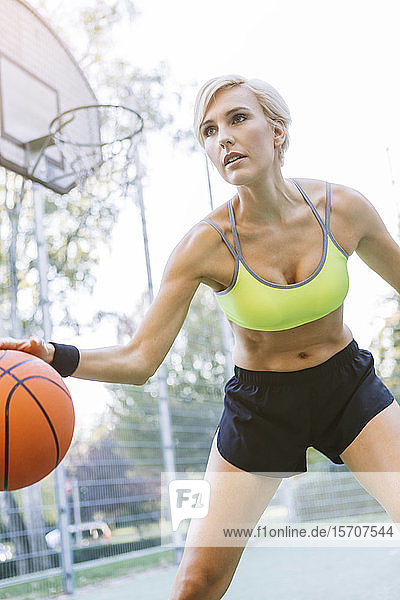 Blonde Frau spielt Basketball  dribbelt