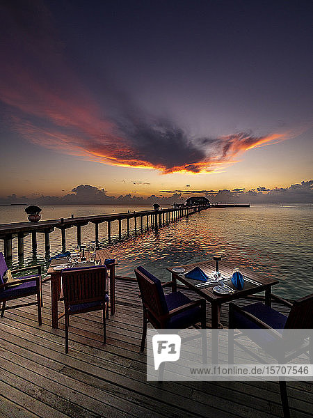 Maldives  Dining tables of coastal restaurant at dusk with pier in background