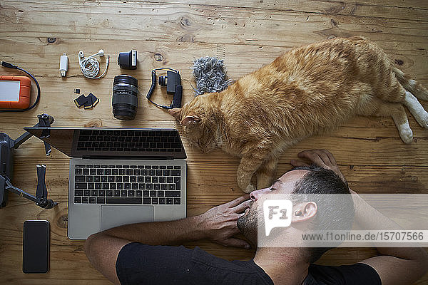 Exhausted man sleeping on table with ginger cat  laptop and photografic equipment