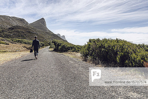 Back view of businessman walking barefoot on country road  Cape Point  Western Cape  South Africa