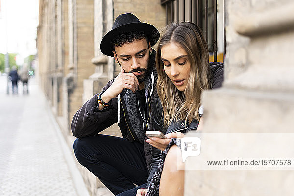 Young couple sitting outdoors looking at cell phone