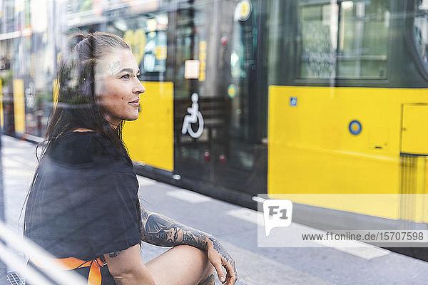 Porträt einer tätowierten jungen Frau  die an einer Straßenbahnhaltestelle wartet  Berlin  Deutschland