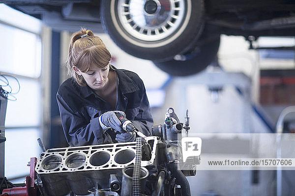 Automechanikerin repariert Auto in Reparaturwerkstatt