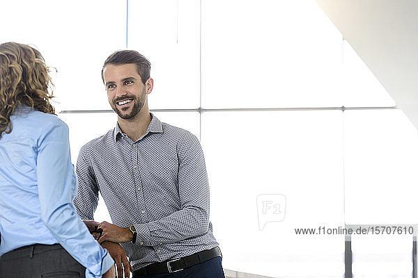 Lächelnder Geschäftsmann und Geschäftsfrau im Gespräch im Amt