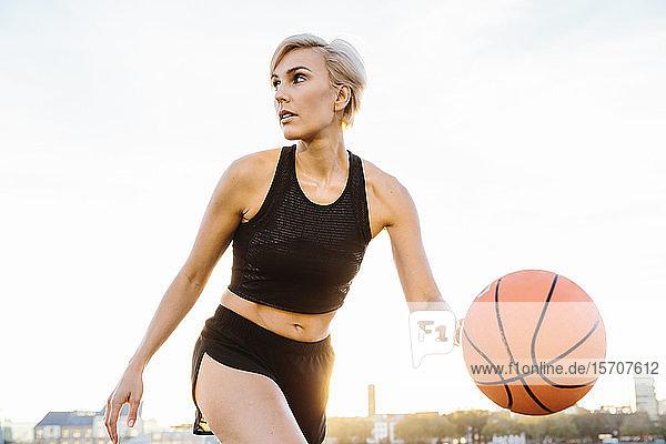 Blonde Frau spielt Basketball  schaut zur Seite