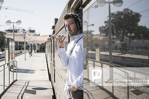 Young man with headphones using smartphone in train door