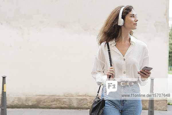 Young woman with smartphone and headphones in the city on the go