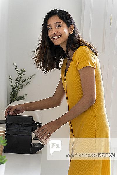 Porträt einer lächelnden jungen Frau  die mit der Kaffeemaschine einen Kaffee kocht