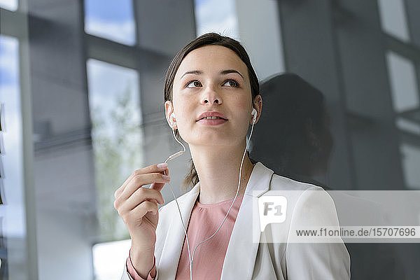 Young businesswoman with earphones in office