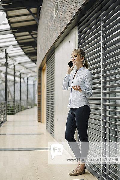 Lächelnde junge Geschäftsfrau am Telefon in einem modernen Bürogebäude