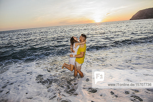 Young couple at the beach during sunset
