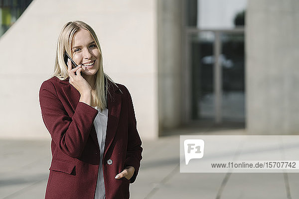 Blond businesswoman using smartphone  looking at camera