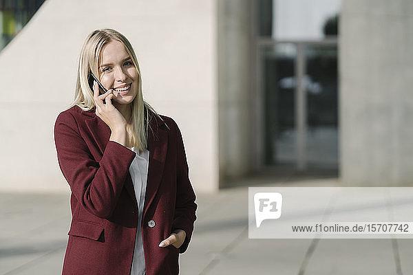 Blonde Geschäftsfrau mit Smartphone  die in die Kamera schaut