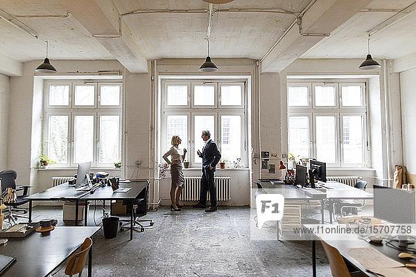 Geschäftsmann und Geschäftsfrau im Gespräch am Fenster im Büro