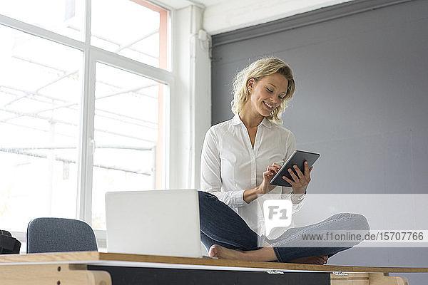 Lächelnde junge Geschäftsfrau sitzt mit Tablett auf dem Schreibtisch im Büro