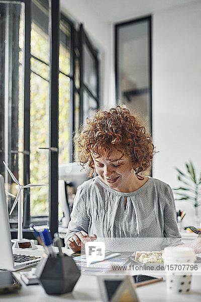 Geschäftsfrau benutzt Smartphone in der Mittagspause im Büro