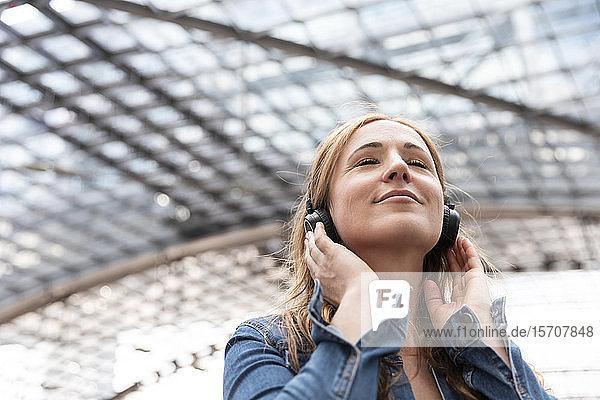 Lächelnde Frau mit geschlossenen Augen  die mit Kopfhörern Musik hört  Berlin  Deutschland