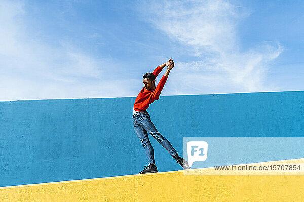 Junger Mann tanzt auf gelber Wand