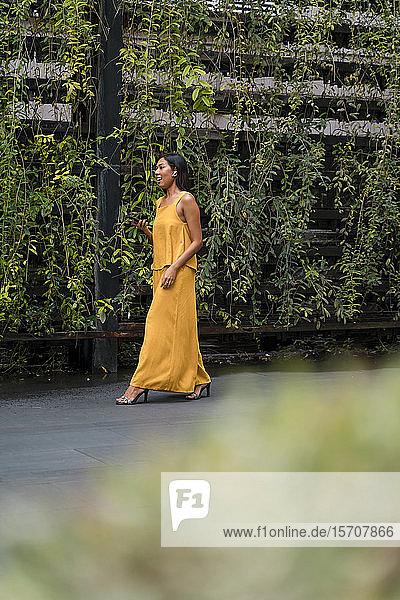 Modisch gekleidete Frau in Gelb telefoniert mit Ohrstöpseln