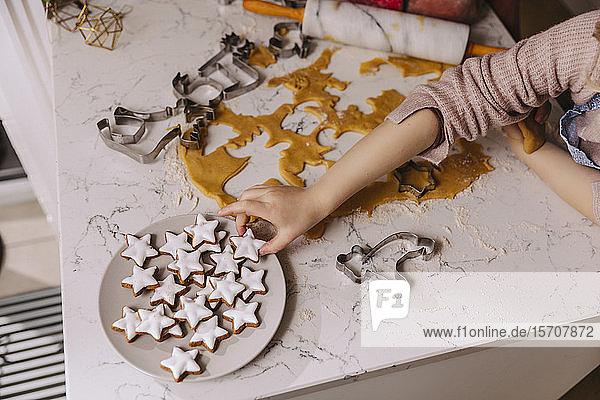 Nahaufnahme eines Mädchens  das Weihnachtsplätzchen vom Teller auf dem Küchentisch nimmt