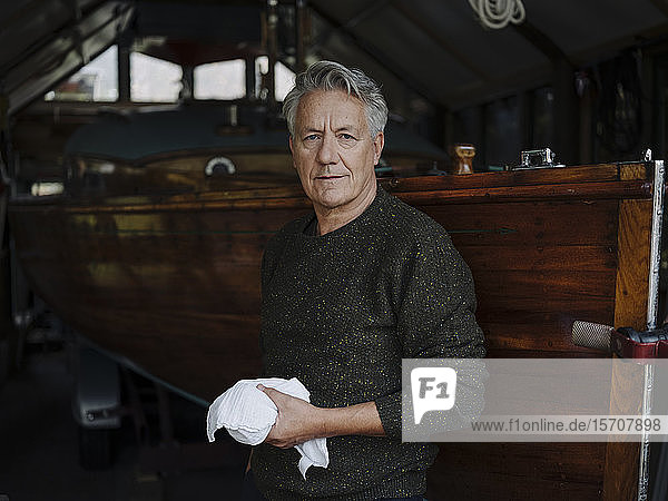 Portrait of a senior man with cloth at wooden boat in a boathouse
