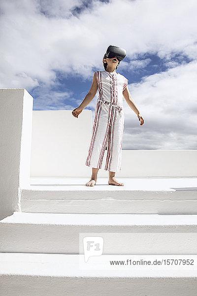 Mädchen steht oben auf einer Treppe und schaut durch eine VR-Brille