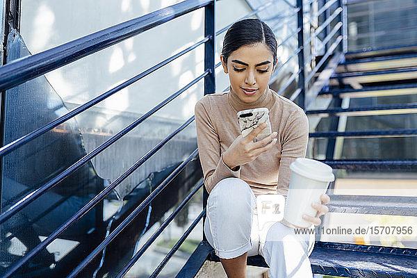 Junge Frau mit Getränk zum Mitnehmen  die auf einer Außentreppe sitzt und ein Smartphone benutzt
