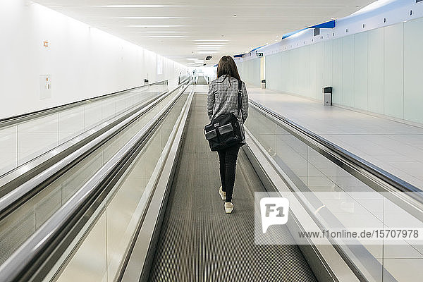 Young businesswoman on moving walkway